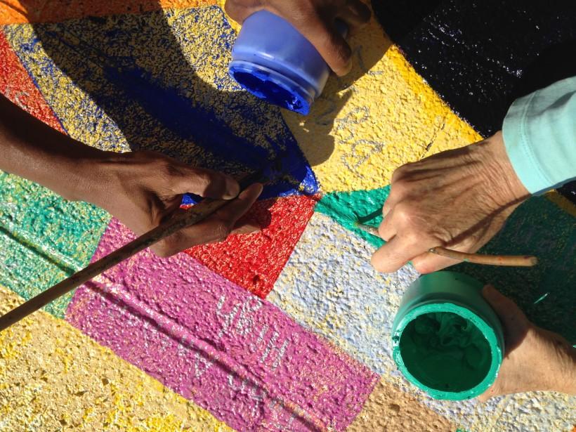 Artists Mary-Linn Hughes and Reginald Zachary restoring the mural