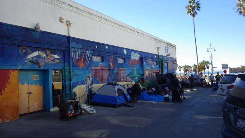 The homeless Venice Community gathers by the wall to make room for the weekly cleaning of Ocean Front Walk.