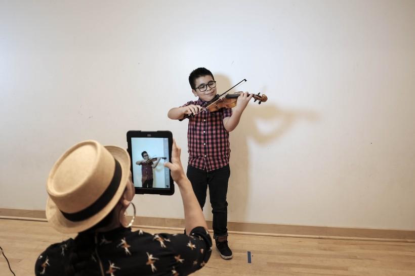 UCLA Mentor photographing JB Arts Student portrait using iPad camera.