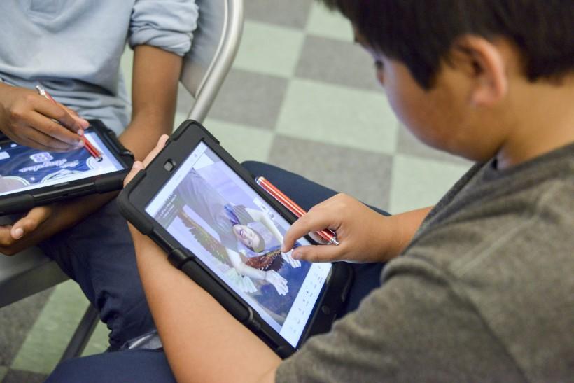JB Arts Student constructing self portrait using Adobe photo-editing programs on iPad.