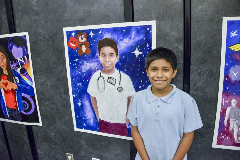 JB Arts Student and his final self-portrait on display at the end of the year assembly.