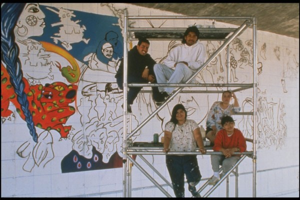 Yreina Cervantes (standing in the center of the scaffolding) during the painting of the original mural in 1989.