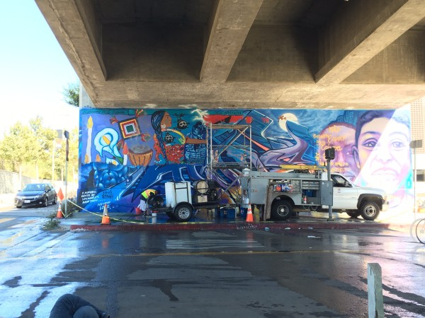 Mural painted over, with left side of La Ofrenda starting to peak through SPARC's MuralShield Process.