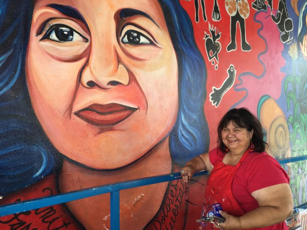 Yreina Cervantes working on the mural in 2016.