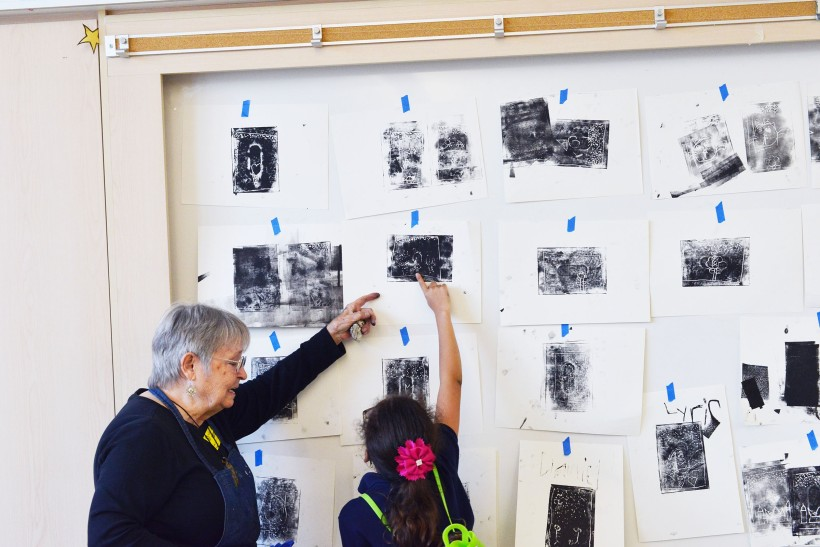Teaching Artist, Kay Brown, and 2nd grade student from Ms. Serratos' class discuss their final prints after a printmaking workshop.