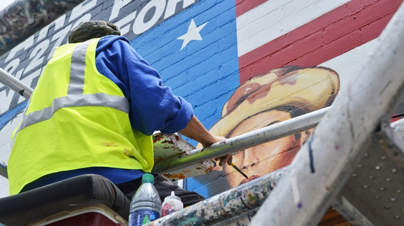 Joe Bravo touches up the portraits int he center of the mural.